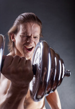 powerfully: Muscular man with dumbbells on black background Stock Photo