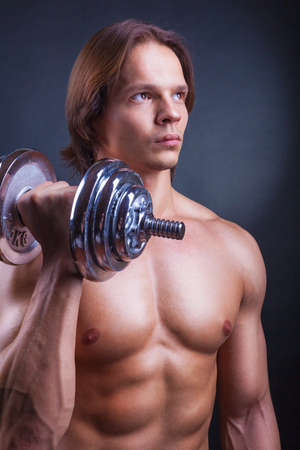 powerfully: Young muscular man with dumbbell on black background Stock Photo