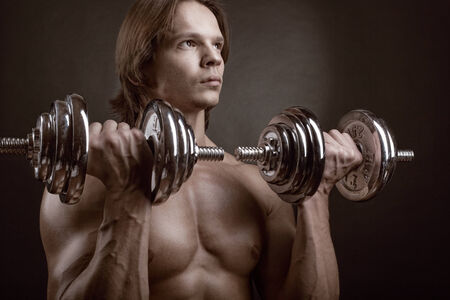 Fit muscular man exercising with dumbbell on dark background photo