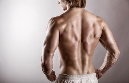 Sterke atletische man terug op een grijze achtergrond