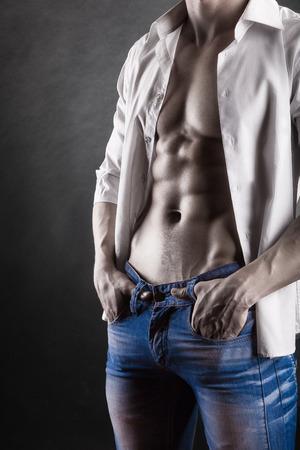 männer nackt: Sexy junger Mann in Hemd auf einem dunklen Hintergrund