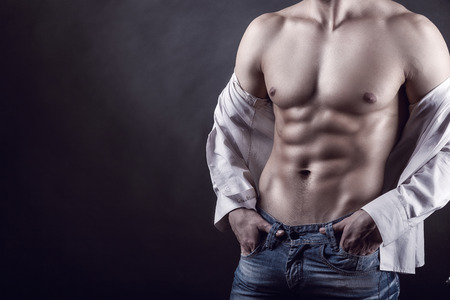 nude abs: Sexy young man in a shirt with a naked torso on a dark background Stock Photo