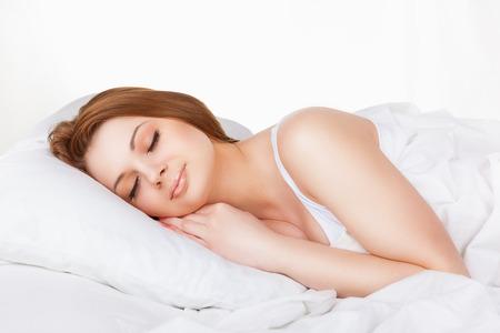 Atraente dormir jovem mulher na cama