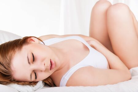 bellyache: Young woman stroking her belly because of bellyache lying on bed