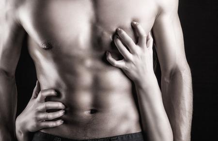 mujeres eroticas: Sexy hombre musculoso y las manos femeninas en un oscuro