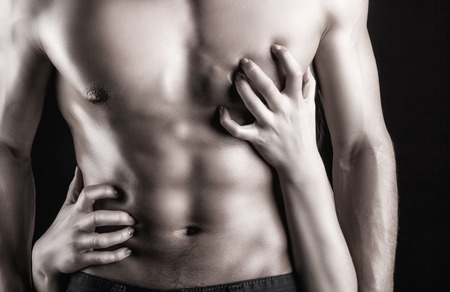 erotic couple: Sexy muscular man and female hands on a dark  Stock Photo