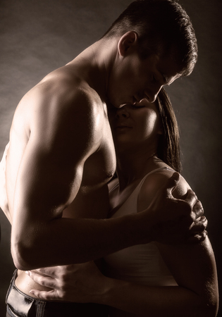erotic woman: Young beautiful loving couple is embracing on a dark  Stock Photo