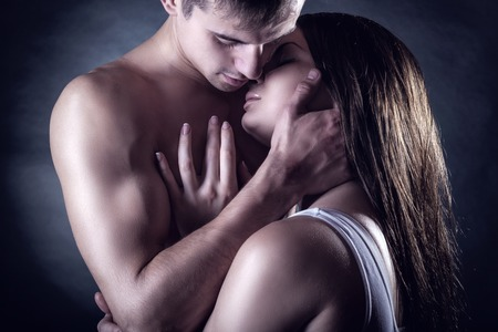 Young beautiful loving couple is embracing on a dark background Stock Photo