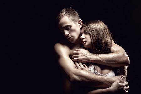 erotic women: Young beautiful loving couple is embracing on a black