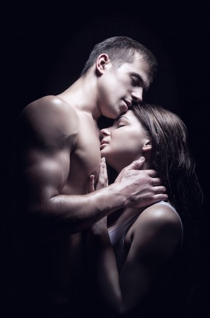 erotic couple: Young beautiful couple in each others arms on a dark