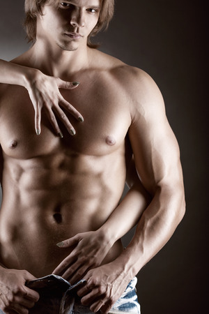 Sexy muscular man and female hands unbuckle his jeans on a dark  Stock Photo