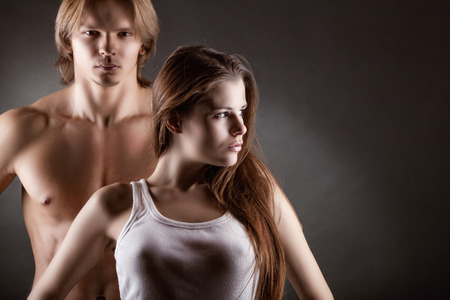 young couple sex: Young sexy girl with a guy on a dark background Фото со стока