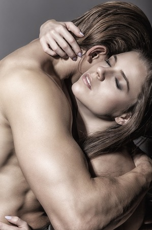 erotic male: Young beautiful couple in each others arms on a dark