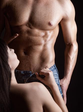 erotico: Giovane donna spogliarsi uomo muscolare su scuro Archivio Fotografico