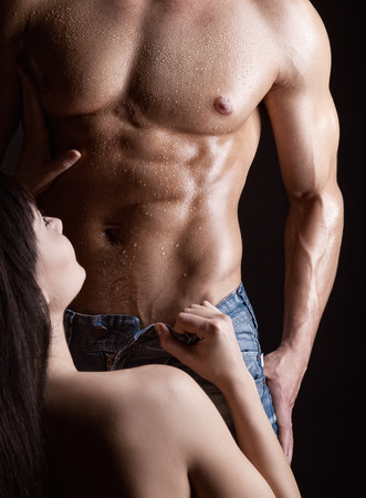 Young woman undressing muscular man on dark