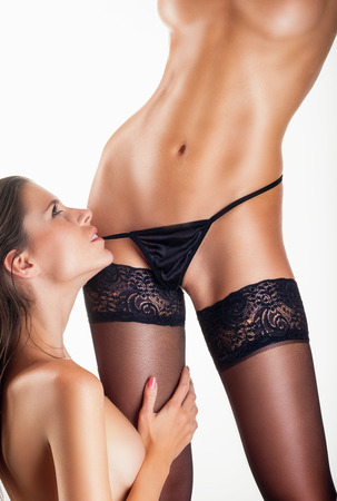 lesbian erotic: Two beautiful lesbian women in erotic foreplay game on a white . Sexy woman pulling black panties