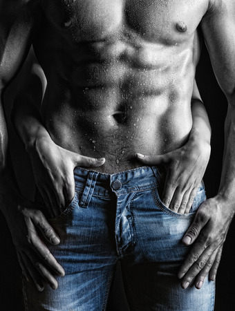 passionate embrace: Sexy muscular man and female hands unbuckle his jeans on a dark  Stock Photo