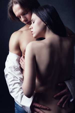 erotic couple: Young beautiful loving couple is embracing on a dark  Stock Photo