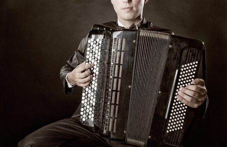 virtuoso: Musician playing the accordion against a black background Stock Photo