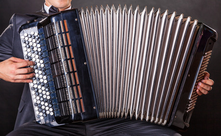 Close-up musician playing the accordion against a black background photo