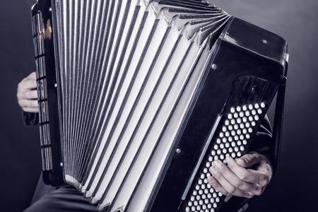 acordeón: Primer plano músico tocando el acordeón sobre un fondo negro Foto de archivo