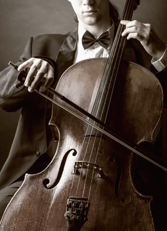 musica clasica: Violonchelista tocando música clásica en el cello en fondo negro Foto de archivo