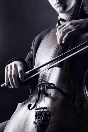 violin player: Cellist playing classical music on cello. Black-and-white photo