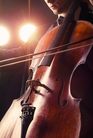 Cellist playing classical music on cello on black background photo