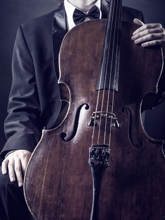 solo violinist: Cellist playing classical music on cello on black background