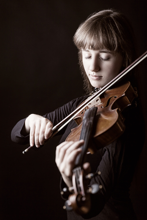 fiddle: Beautiful young woman playing the violin on dark background Stock Photo