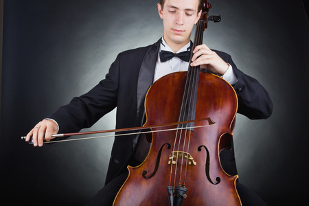 cellos: Cellist playing classical music on cello on black background