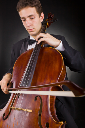 solo violinist: Cellist playing classical music on cello on black background. Focus on the cello