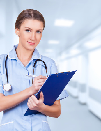 Young medical doctor woman in the office with stethoscope and clipboard photo