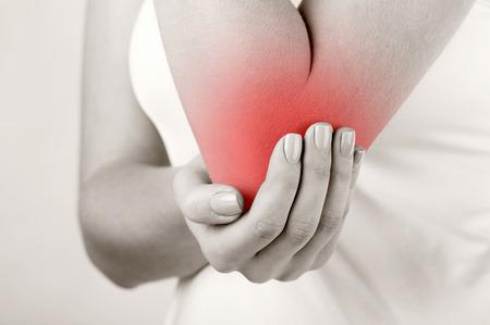 masaje deportivo: Mujer con dolor en el codo aislado en fondo blanco