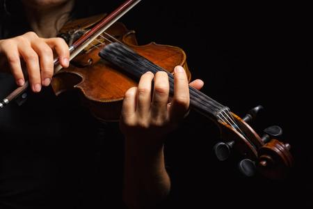 violines: Tocar el violín. Instrumento musical con manos de ejecutante sobre fondo oscuro. Foto de archivo