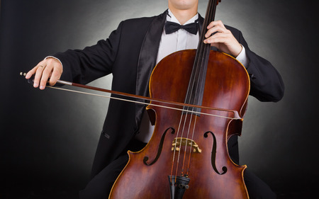 classical music: Cellist playing classical music on cello on black background
