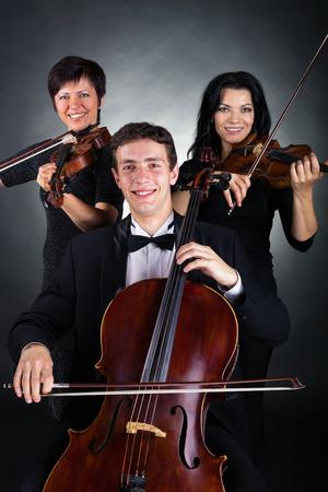 violinista: Dos violinista y violonchelista jugaron en un fondo oscuro