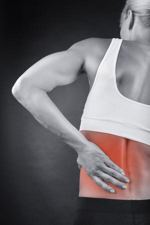 deportistas: Mujer con dolor de espalda sobre un fondo negro Foto de archivo