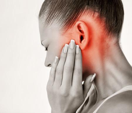 oreja: Mujer joven con dolor de o�do, de la mano en la cabeza. Aislar en el fondo blanco