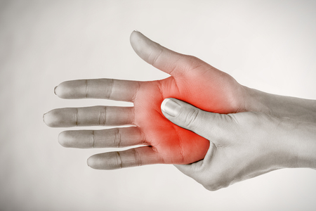 A young woman massaging her painful hand on a gray background