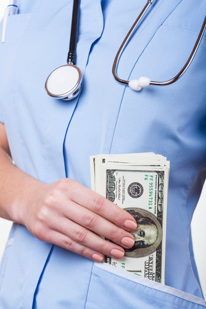 doctor giving dollars: Female doctor with money in his pocket a blue robe Stock Photo