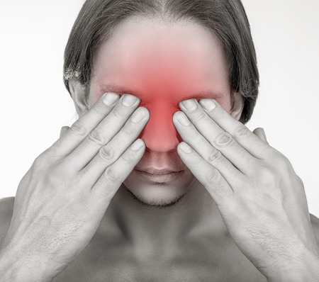 pangs: A young man suffering from pain in the eyes. Isolated on white background Stock Photo