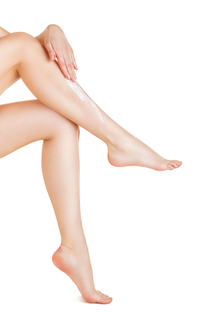 lotions: Applying moisturizer cream on the legs  isolated on white background Stock Photo