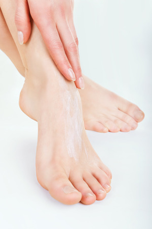 bare women: Close-up woman applying moisturizer cosmetic cream on foot on light background Stock Photo