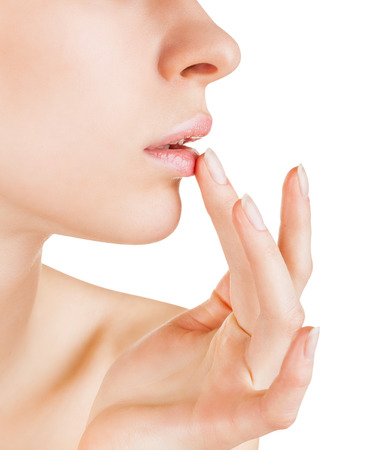Attractive young woman applying lip balm isolated on a white background Foto de archivo