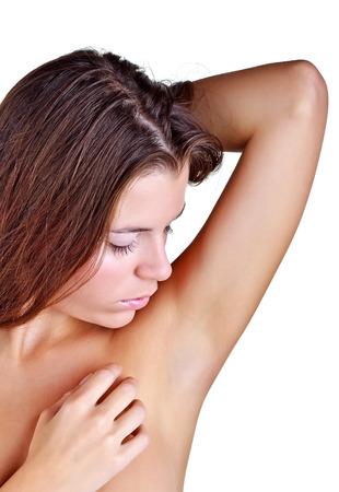 armpit: Beautiful girl looks armpit, isolated on white background Stock Photo