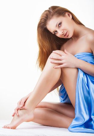 beautiful legs: Beautiful young woman after bath sitting on the floor and stroking her legs on white background Stock Photo