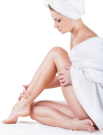 Schöne junge Frau im Handtuch auf dem Boden sitzen und streichelte ihre Beine isoliert auf weißem Hintergrund