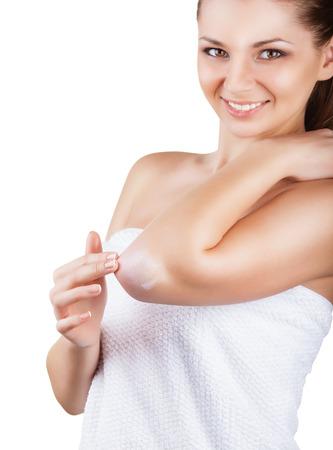 codo: Primer plano de una mujer cuida de sus codos usando crema cosmética