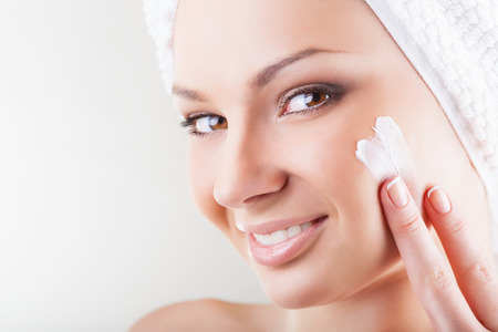 Close-up beautiful woman applying moisturizer cosmetic cream on face on light background Standard-Bild